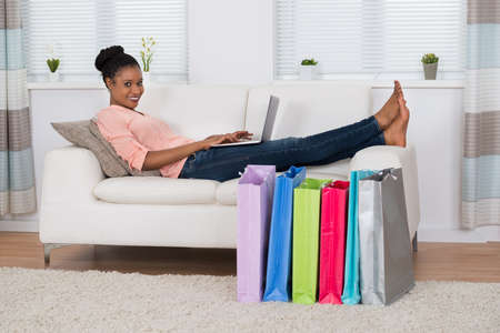 surf shop: Portrait Of A Smiling African Woman Using Laptop For Shopping