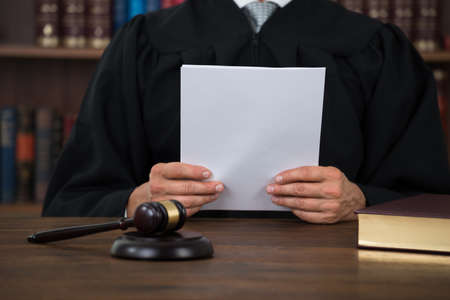 Midsection of judge reading document at desk in courtroom Stock Photo