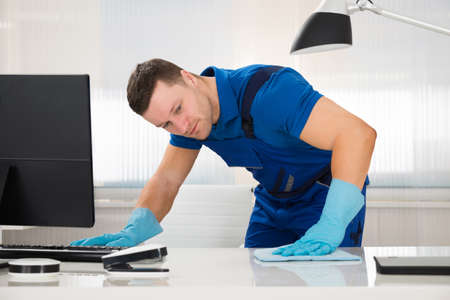 mid adult male: Mid adult male worker cleaning desk with sponge at office Stock Photo