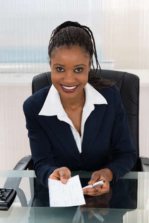 happy african: Portrait Of A Young Businesswoman Offering Cheque Stock Photo