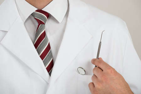 dentist at work: Midsection of dentist with tools in pocket against white background