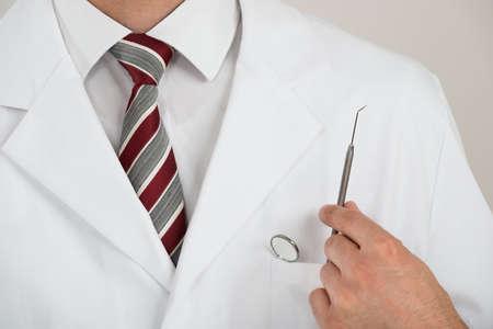 dentista: Secci�n media de dentista con herramientas en el bolsillo contra el fondo blanco