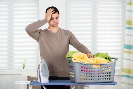 tired: Tired man looking at laundry basket on ironing board at home