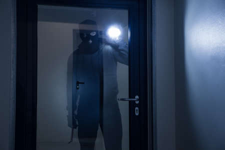 Thief with flashlight trying to break glass door with crowbar Reklamní fotografie - 50691820