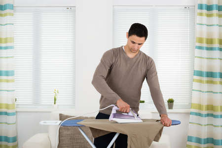 front house: Young man ironing tshirt on board against windows at home Stock Photo