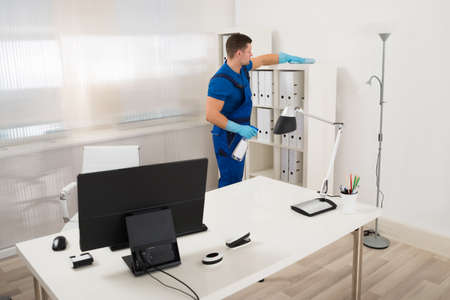 mid adult male: Mid adult male worker cleaning shelf with spray and sponge at office Stock Photo