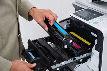 cartridges: Cropped image of businessman fixing cartridge in photocopy machine at office