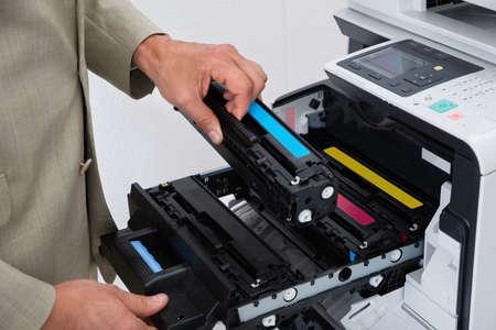 fotocopiadora: Imagen recortada de cartucho de fijación hombre de negocios en la fotocopiadora en la oficina