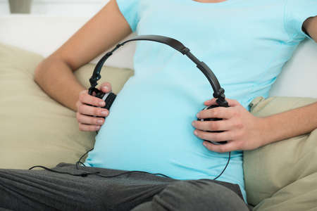 midsection: Midsection of pregnant woman placing headphones on stomach at home Stock Photo