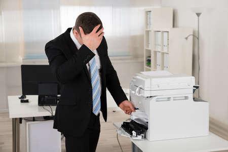 mermelada: hombre de negocios irritada mirando el papel atascado en la impresora en la oficina