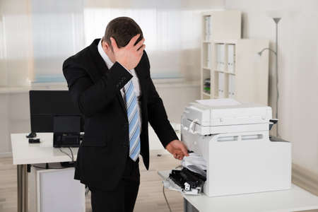 problem: Irritated businessman looking at paper stuck in printer at office