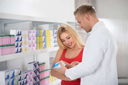 medicine box: Young male pharmacist showing medicine box to female customer in pharmacy