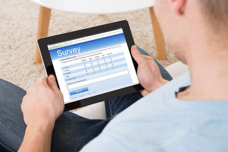 online survey: High angle view of man filling survey form online on digital tablet at home Stock Photo