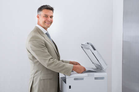 photocopy: Side view of businessman keeping paper on photocopy machine in office