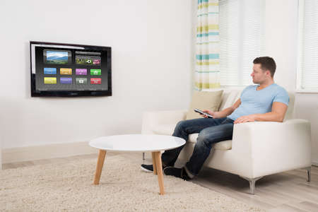 one man: Full length of mid adult man with remote control watching television at home