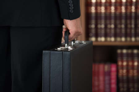 business briefcase: Midsection rear view of businessman carrying briefcase in office