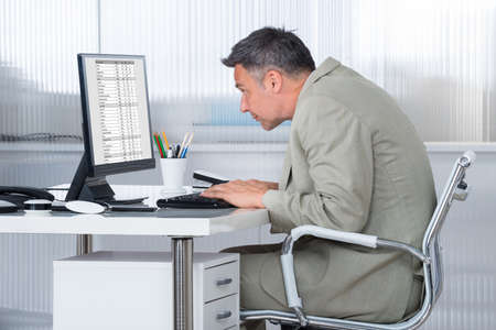 financial audit: Side view of concentrated businessman using computer at desk in office Stock Photo