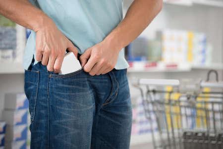 Mittlerer Teil der männlichen Ladendieb Putting-Paket in der Tasche am Supermarkt Standard-Bild