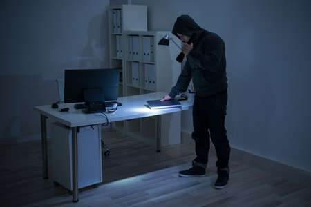 intruding: Full length of robber with flashlight holding laptop at desk in office Stock Photo