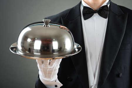 Buik van ober met dienblad met glazen kap tegen een grijze achtergrond Stockfoto