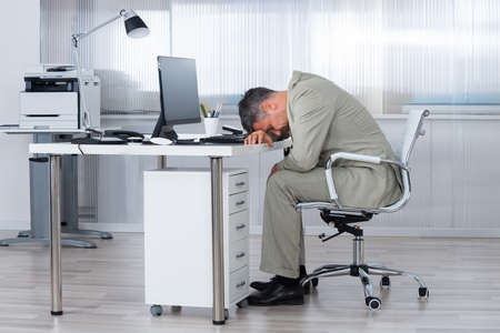 tired businessman: Side view of tired businessman sleeping on desk in office