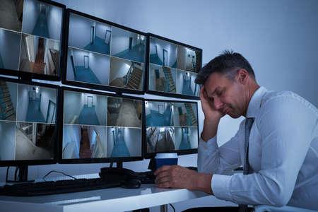 Volwassen beveiligingssysteem exploitant slapen terwijl leunend op bureau in het kantoor
