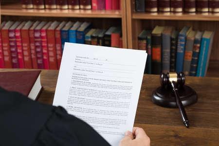 martillo juez: Vista de �ngulo alto de juez de sexo masculino lectura de documentos legales en el escritorio en sala Foto de archivo