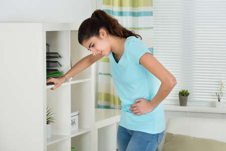 Young woman suffering from stomach ache leaning on shelves at home
