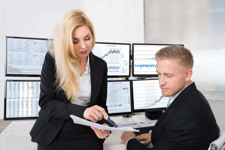 multiple: Young financial analysts discussing over documents in office