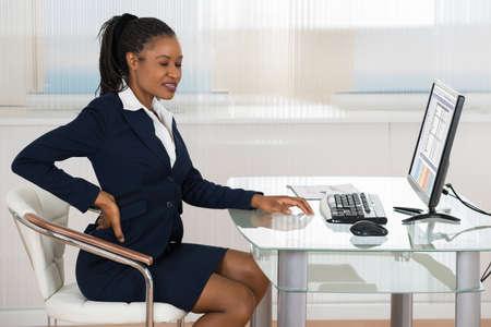 Retrato de una empresaria africana joven que sufre de dolor de espalda