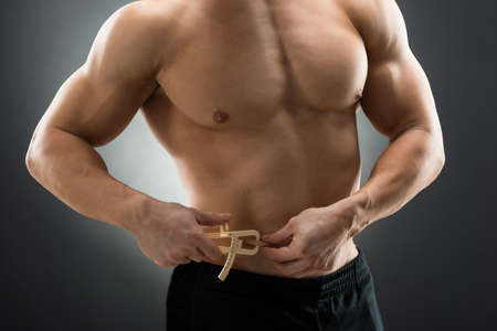pinch: Midsection of muscular man measuring fats with caliper against black background Stock Photo