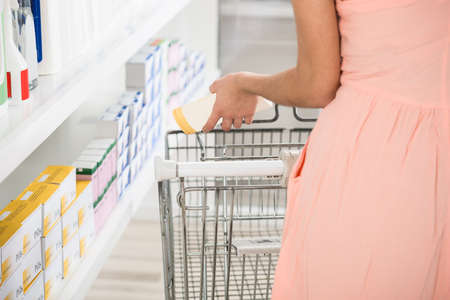 woman shopping cart: Midsection rear view of woman with shopping cart buying beauty product in store Stock Photo