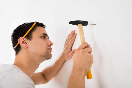 hammering: Side view of young man hammering nail on white wall at home