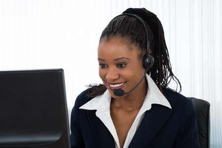 ヘッドセットで話している若い笑顔の実業家の肖像画