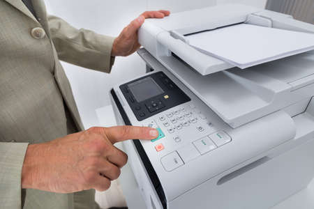 midsection: Midsection side view of businessman pressing printers button in office
