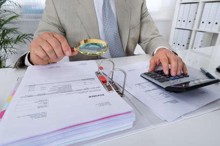 Sezione centrale di ragioniere maschio usando la calcolatrice mentre si tiene la lente di ingrandimento per analizzare fatture in ufficio Archivio Fotografico