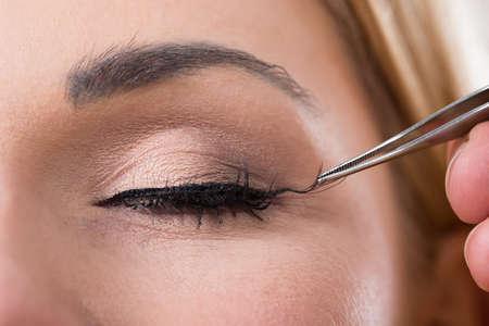 pestaÑas postizas: Recortada mano poniendo pestañas falsas en el ojo de la mujer