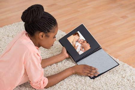 Jeune femme africaine souriant tout en regardant un album de photos dans le salon