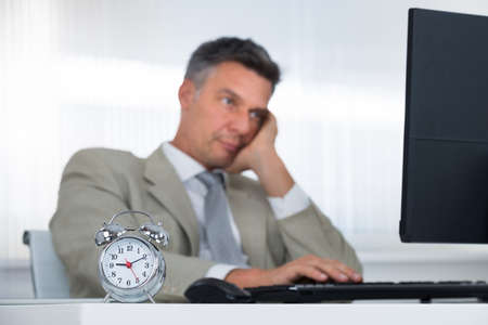 late 40s: Tired businessman using computer at desk with focus on clock in office