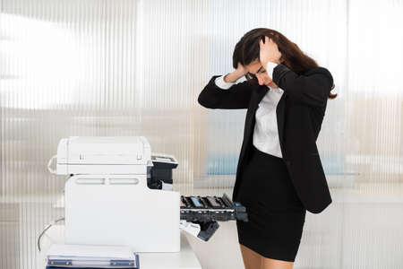 Irritated young businesswoman looking at printer machine at office