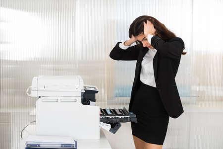 impresora: Irritada joven empresaria mirando a la máquina impresora en la oficina