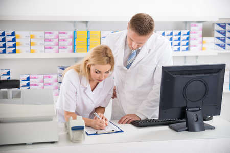 Young male and female pharmacists maintaining checklist at counter in pharmacy