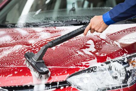 Bijgesneden afbeelding van volwassen wasmachine schoonmaken rode auto op tankstation Stockfoto