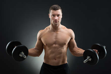 man gym: Portrait of confident muscular man holding dumbbells while standing against black background