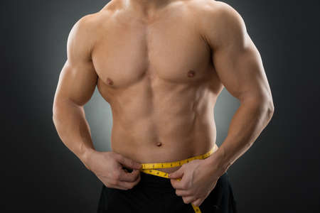 man gym: Midsection of muscular man measuring waist with measure tape against black background