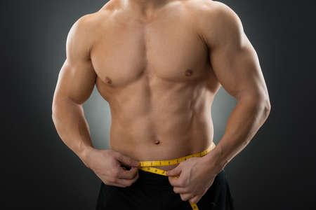 cintura: Sección media de hombre muscular medir la cintura con cinta de medida contra el fondo negro Foto de archivo