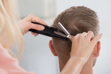 man haircut: Rear view of young man getting haircut from female hairdresser at salon