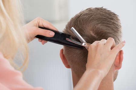 Vista posteriore della giovane uomo ottenere taglio di capelli dal parrucchiere femminile al salone Archivio Fotografico