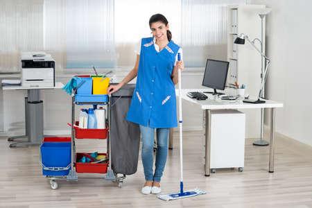 office uniform: Full length portrait of happy female janitor mopping floor in office