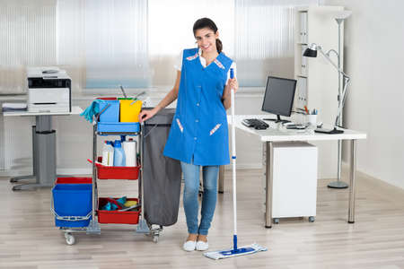 Portrait en pied de femme heureuse étage concierge de ratissage dans le bureau